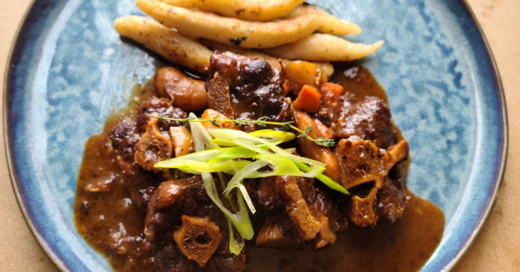 Saucy oxtail garnished with scallions and accompanied by spinners