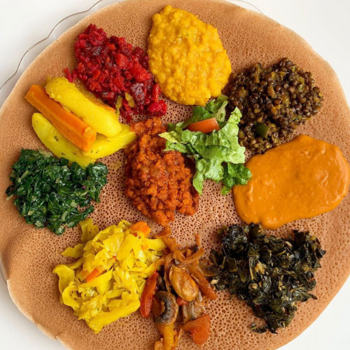 a platter of injera with various vegetable stews