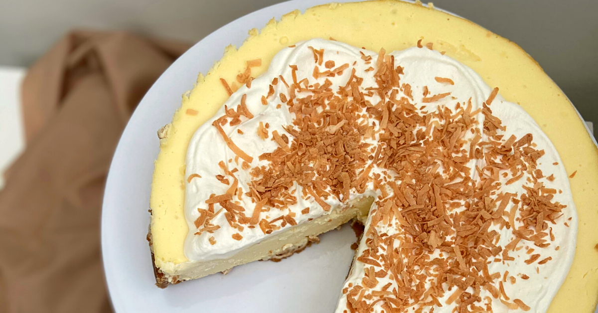 a round, pale yellow cheesecake with a slice cut out of it, topped with soft whipped cream and sprinkles of toasted coconut