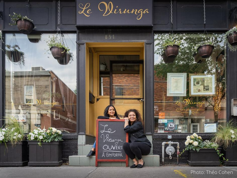 "Two women sitting outside a restaurant, leaning on a chalkboard sign that says ""Le Virunga OUVERT À EMPORTER"""