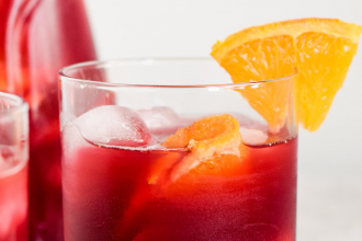 photo of a red drink in a stout glass with ice and a sliver of orange on the rim