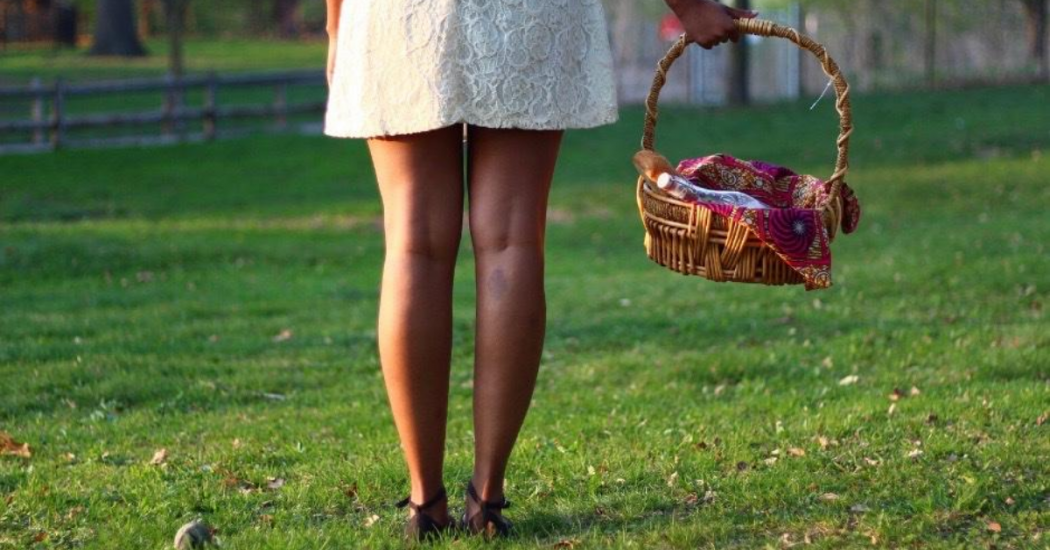 Pictured: The lower half of a Black girl in a short white dress holding a picnic basket in a grassy area.