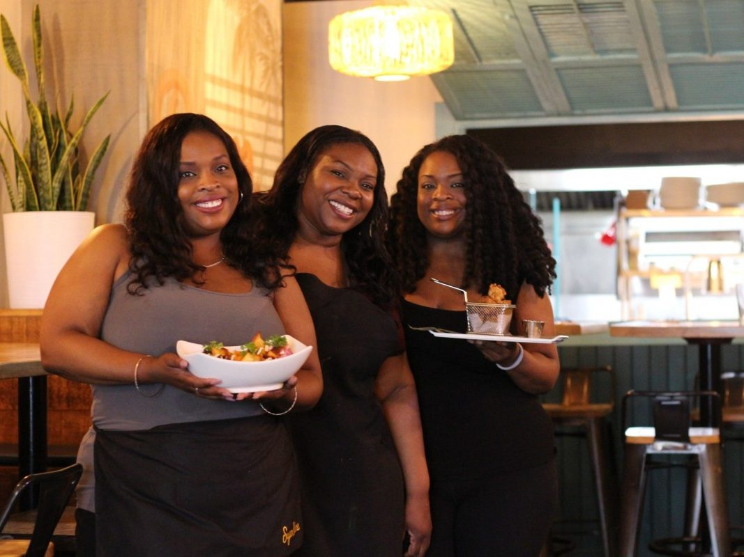 Three Black women holding plates of food in a restaurant