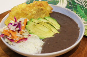 BLACK FOODIE - Haitian Sos Pwa Nwa in a white bowl with sliced avocado, pikliz, and fried plantains