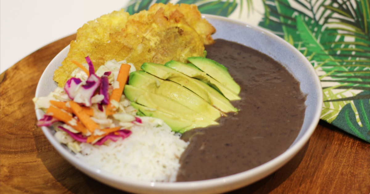 a bowl of creamed black beans with white rice, fried plantains, avocado, and pickled cabbage on the side