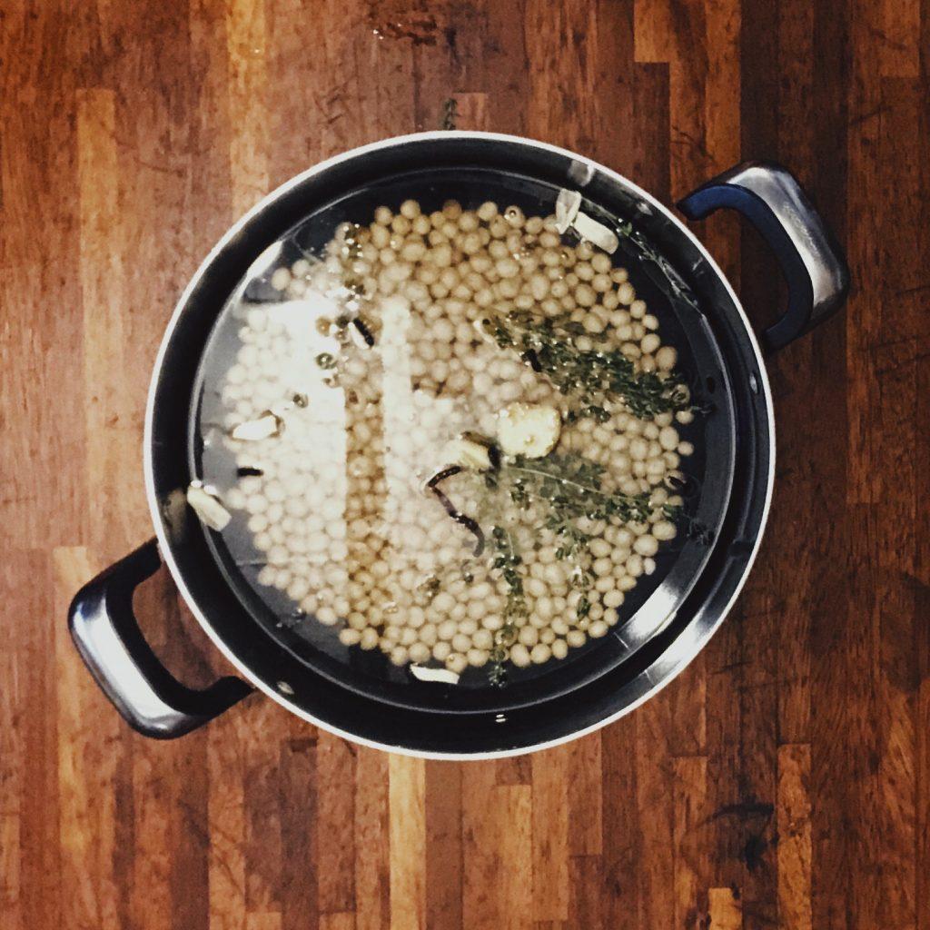A pot containing Bambara beans, water and aromatics.