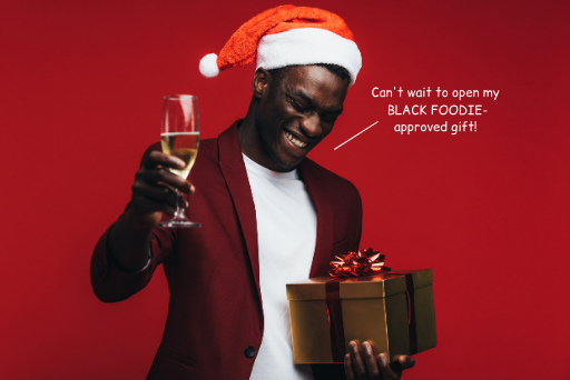 "Black man wearing a Santa hat, holding a present and a glass of champagne. Text on image says ""Can't wait to open my BLACK FOODIE-approved gift!"