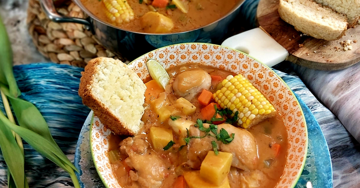 a bowl of brightly coloured stew with corn, sweet potato, and carrot pieces, chicken, and a slice of thick bread