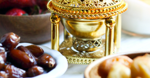 a bowl of dates in front of a gold candle ornament on a table
