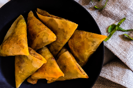 a black plate of crispy fried samosas for iftar