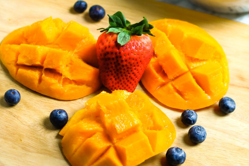slices of mango, a strawberry, and blueberries on a wooden platter