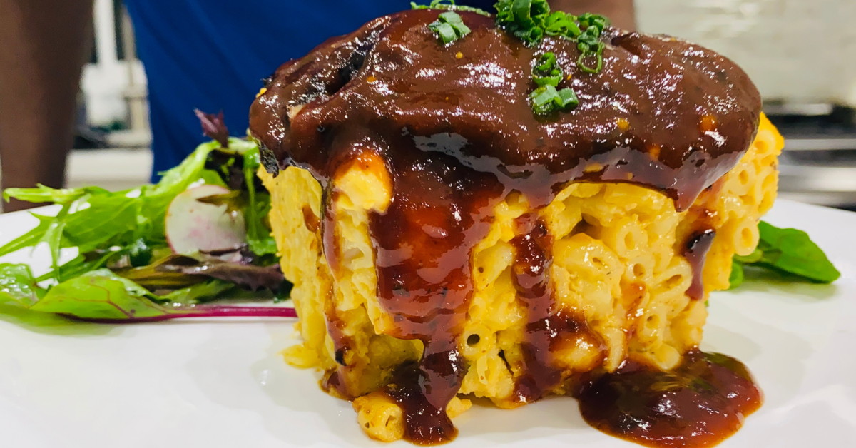 a slice of macaroni pie topped with a portobello mushroom covered in BBQ sauce