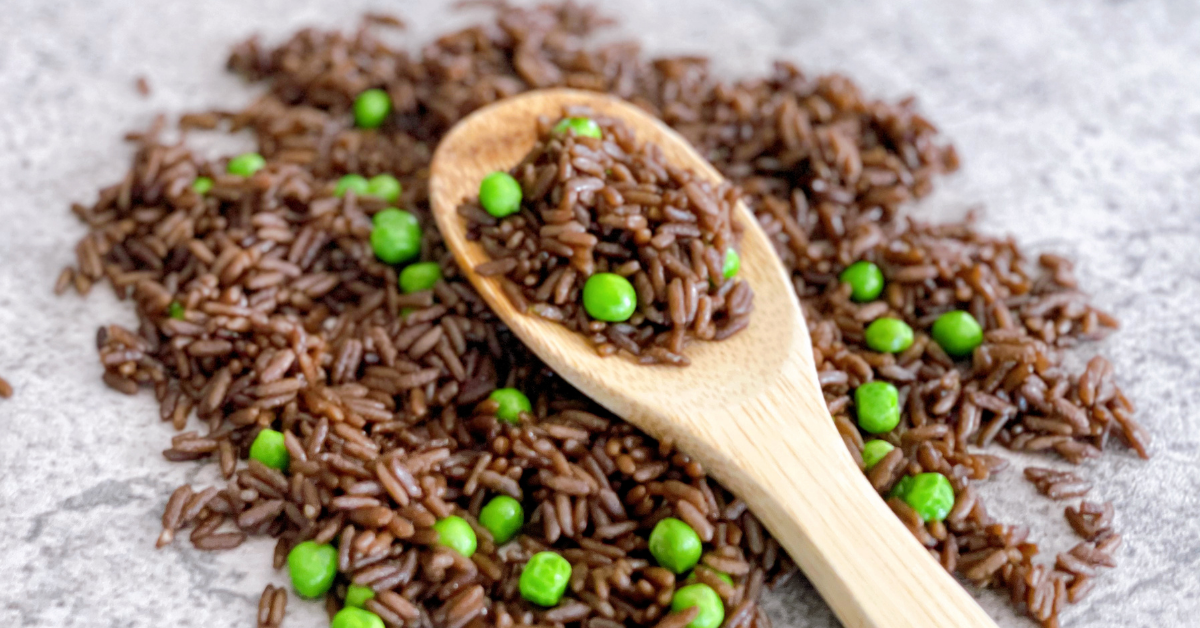 A serving of dark brown rice with bright green peas spread on a marble countertop. A wooden spoon with a portion of rice sits on top.