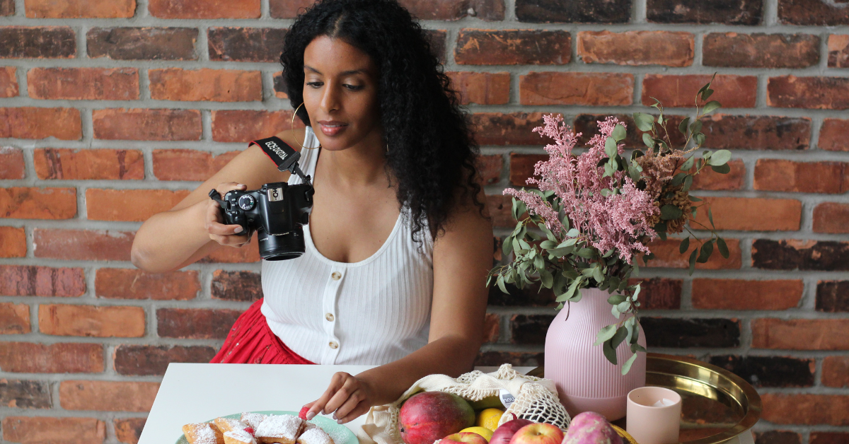 a Black girl sitting at a table and holding a camera up high to take a picture of food on a plate