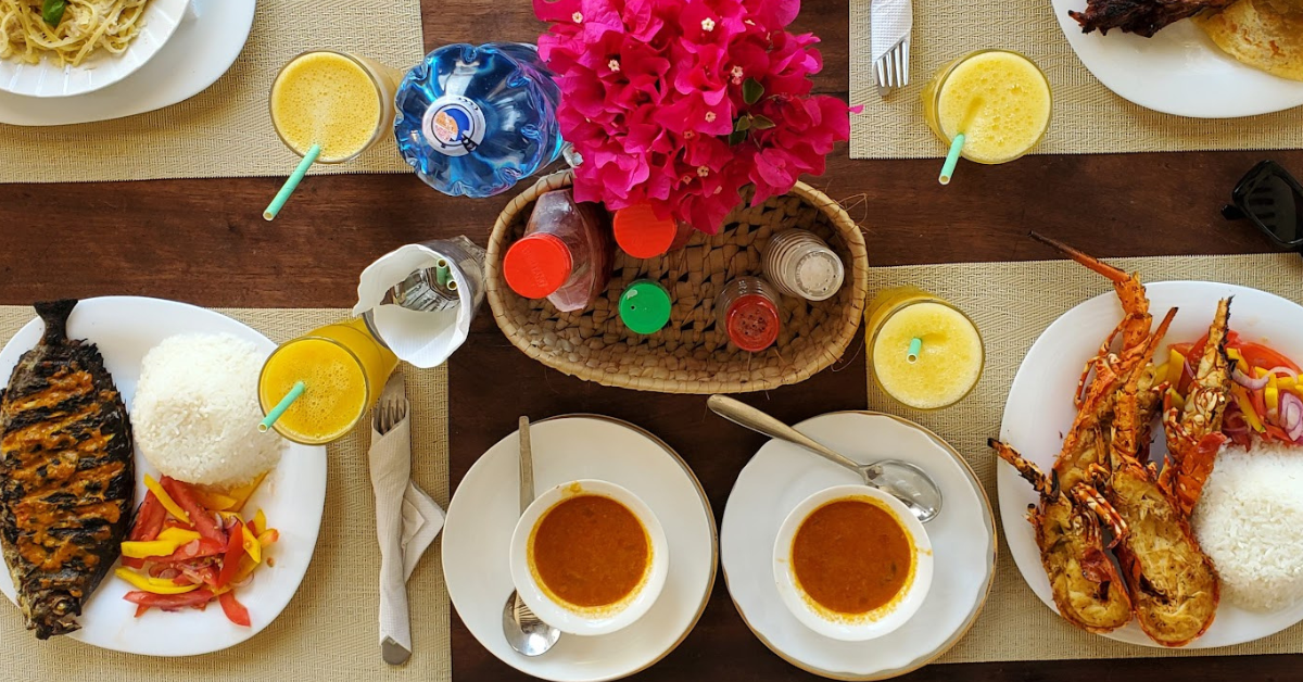 a table top with pink flowers in the centre, 4 glasses of orange juice, and two plates wih rice, fish, and vegetables